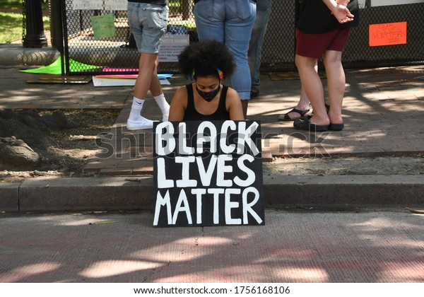 Washington, D.C./USA - June 13, 2020: Protester rests on a curb with a Black Lives Matter sign in front of the White House during a Black Lives Matter Protest