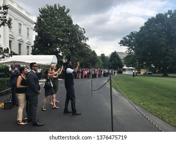 Washington DC,USA - June 16,2017:Staff, media and tourists watching over the presidential helicopter = Marine One flying from the grass square on the south side of the White House.