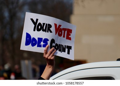 WASHINGTON, DC/USA- MARCH 24, 2018: A protester holds a sign encouraging voting in the next election at the March For Our Lives student demonstration in Washington, DC on March 24, 2018.