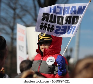 WASHINGTON, DC/USA - MARCH 24, 2018: A little boy, on his father's shoulders, holds a March For Our Lives flag during the Pennsylvania Avenue protest for gun reform in Washington, DC on March 24, 2018