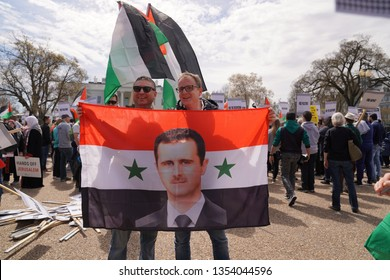 Washington, DC/USA – March 24, 2019: Two demonstrators holding a Syrian flag super imposed with the image of President Bashar al-Assad at an anti-AIPAC demonstration at the White House.