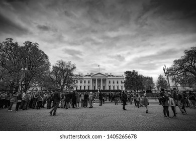 Washington, District of Columbia / United States – April 17, 2017:  Tourists walk in front of the White House on Pennsylvania Avenue.
