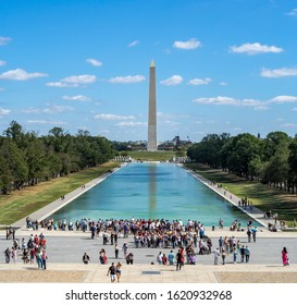 Washington, District of Columbia, United States of America - summer 2020 : [ Washington monument park, obelisk on national mall, American flags and US capitol ]