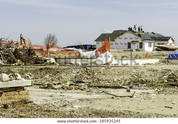 WASHINGTON, ILLINOIS, USA - MARCH 31, 2014: Roofers repair a house near the exposed foundation of another blasted by a tornado on November 27, 2013 that devastated entire neighborhoods here.
