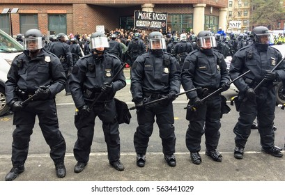 """WASHINGTON, Jan. 20, 2017 -- Police in riot gear form a line around detained #DisruptJ20 protesters holding a """"Make Racists Afraid Again"""" banner during the presidential inauguration of Donald Trump."""