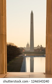Washington Monument and Capitol as seen between columns of Lincoln Memorial at sunrise - Washington DC USA