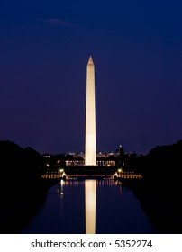 Washington Monument in Washington, DC, beautifully illuminated at night and reflecting in the reflecting pool. As seen from the steps of the Lincoln Memorial.