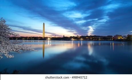Washington Monument at night with the city skyline and cherry blossom. Colorful reflections of Washington landmarks in the Tidal Basin.