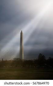 WASHINGTON MONUMENT WITH SUN LIGHT BEAMS THROUGH THE SKY AND A FLOCK OF FLYING BIRDS, WASHINGTON DC, CAPITAL CITY OF AMERICA (LOW LIGHT TONE)