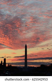 Washington Monument at sunset with commercial airliner flying above