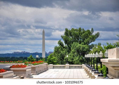 The Washington Monument towers above the background landscape on a cloudy summer day on the National Mall in Washington DC. View from the east front of the United States Capital building.