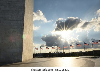 Washington Monument wall with american flags during sunset light, Washington DC