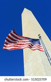 Washington Monument with waving American Flag in foreground, Washington DC, USA