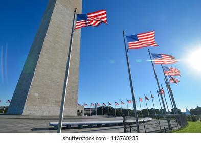 Washington Monument with waving United States flags on flagpoles - Washington DC United States