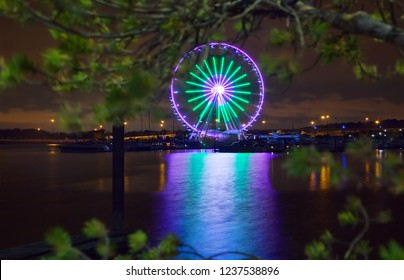 Washington National Harbor, Maryland, USA - August 19, 2018: Illuminated Ferris wheel at night  in National Harbor on Potomac River