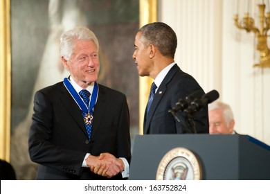 Washington - November 20: Former President Bill Clinton shakes hands with President Obama after receiving the Presidential Medal of Freedom at The White House on November 20, 2013 in Washington, DC.