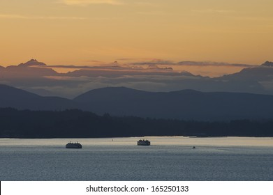Washington State Ferries and the Olympic Mountains. At sunset, two ferryboats pass each other on their commuter routes from Seattle to Bainbridge Island, Washington.