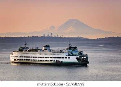washington state ferry crossing in front of mt rainier and seattle.