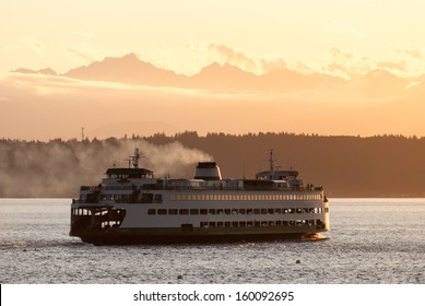 A Washington State ferry with the Olympic Mountains in the distance.