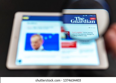 Washington, USA - April 09, 2019: The Guardian News website homepage on the tablet screen. Guardian News channel logo visible  through a magnifying glass. Can be used as marketing or business concept