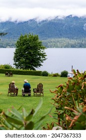 Washington, USA - July 8, 2021: An adult couple relaxes on adirondack chairs near the lake at the Lake Quinault Lodge on a foggy morning