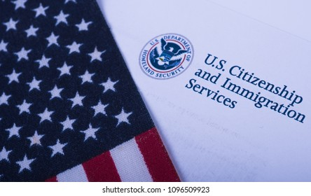 Washington,DC- March, 5, 2018: American flag next to Envelope from USCIS (Department of homeland Security - United States Citizenship and Immigration Services). Official department (Government) Logo.