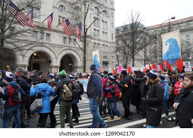 Washington/USA – January 19, 2019: Demonstrators march past the Trump Hotel on Pennsylvania Avenue at the 2019 Women's March.