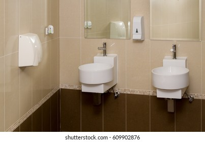 A washroom showing basins, a wall mounted hand dryer, mirrors and soap dispenser