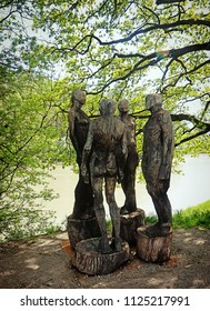 """WASSERBURG, GERMANY - APRIL 22, 2018 - """"social animal"""",  wooden sculpture group by Jørgen May under the trees of the promenade along the Inn river"""