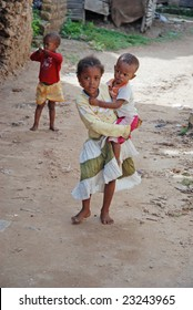 WASSINI ISLAND, KENYA, AFRICA, DECEMBER 2008: A little African girl from a poor fishermen's village comes out holding her little brother, during visit of a humanitarian group.
