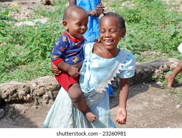 WASSINI ISLAND, KENYA, AFRICA, DECEMBER 2008: Happy African girl from a poor fishermen's village holding her little brother, during visit of a humanitarian group.