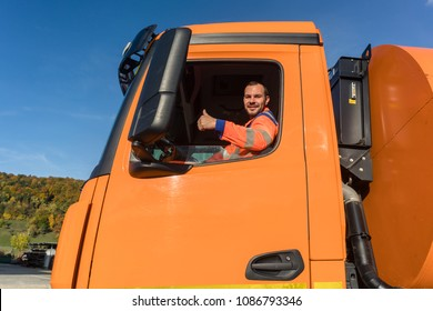 Waste collector driving Garbage truck giving thumbs up from the window