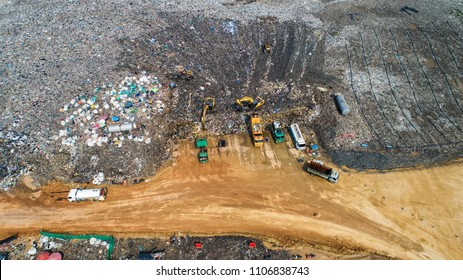 A lot of waste is disposed of in the waste disposal pits. Loaders is working on a mountain garbage. Aerial view and top view.