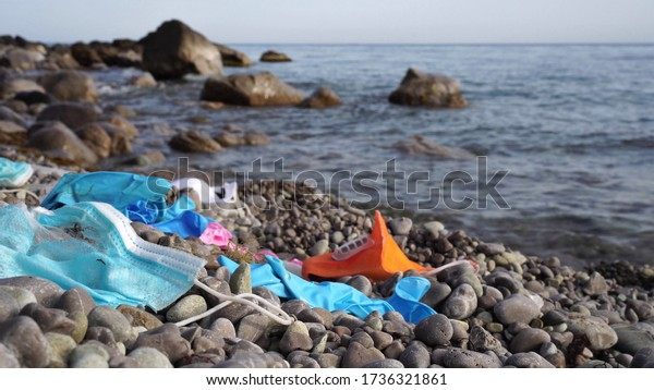 Waste during COVID-19. Discarded to ocean coronavirus single-use face masks and usesd latex gloves. Environmental and ocean plastic pollution