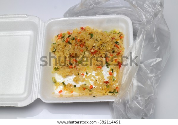 Waste foam food containers with rice blown out food.