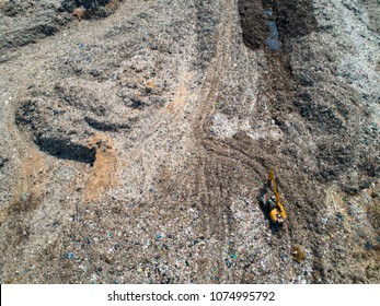 Waste from household in waste landfill. waste disposal in dumping site. excavator machine is working on a mountain garbage. aerial view and top view.