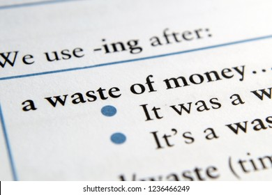 Waste of money phrase in English textbook Selective focus