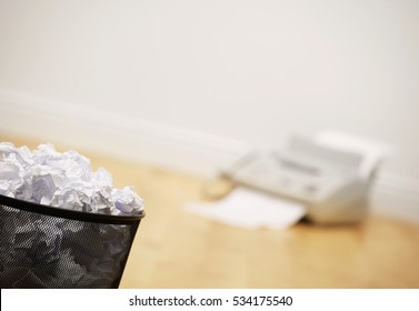 WASTE PAPER BIN FULL OF CRUMPLED PAPER AND FAX MACHINE ON WOOD OFFICE FLOOR