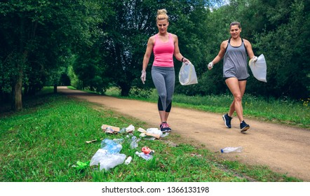 Waste pile and two girls running with bags doing plogging outdoors