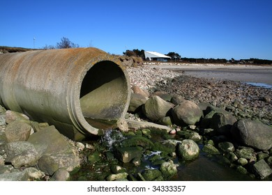 waste pipe or drainage polluting environment. concrete pipes by beach