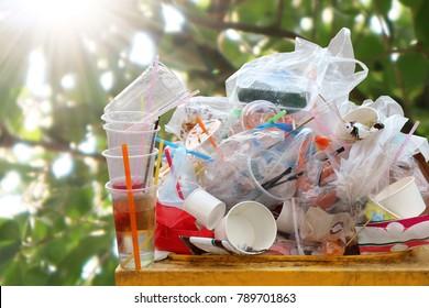 Waste plastic heap at bin, Trash full bin waste garbage, Garbage Plastic bag waste Lots of junk on nature tree sunshine background, Garbage many close-up