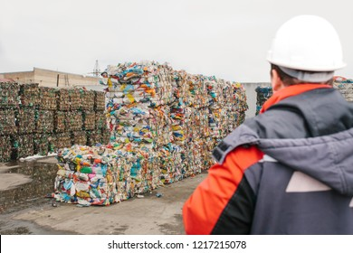 Waste processing plant. Technological process for acceptance, storage, sorting and further processing of waste for their recycling. Selective focus. The worker is out of focus or blurred.