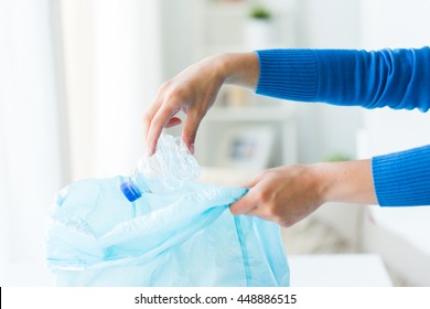 waste recycling, reuse, garbage disposal, environment and ecology concept - close up of hand putting empty used crashed plastic water bottles into rubbish bag at home