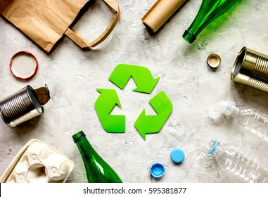waste recycling symbol with garbage on stone background top view