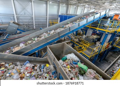 Waste sorting plant conveyors filled with various household waste. Modern waste processing.