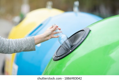 Waste Sorting And Recycling Concept. Unrecognizable female throwing empty glass bottle into green recycle bin garbage container outdoors, caring about environment, cropped image with selective focus