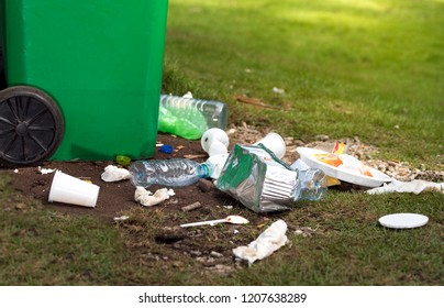 waste spilling on ground when dustbin full in park, grass