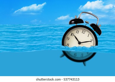 Waste of time concept, alarm clock on the water