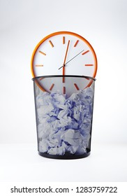 Wastebasket and wall clock.