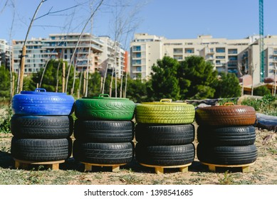 Wastebaskets to recycle paper, plastic and organic materials made with old recycled tires and painted colors, concept of sustainability and recycling.